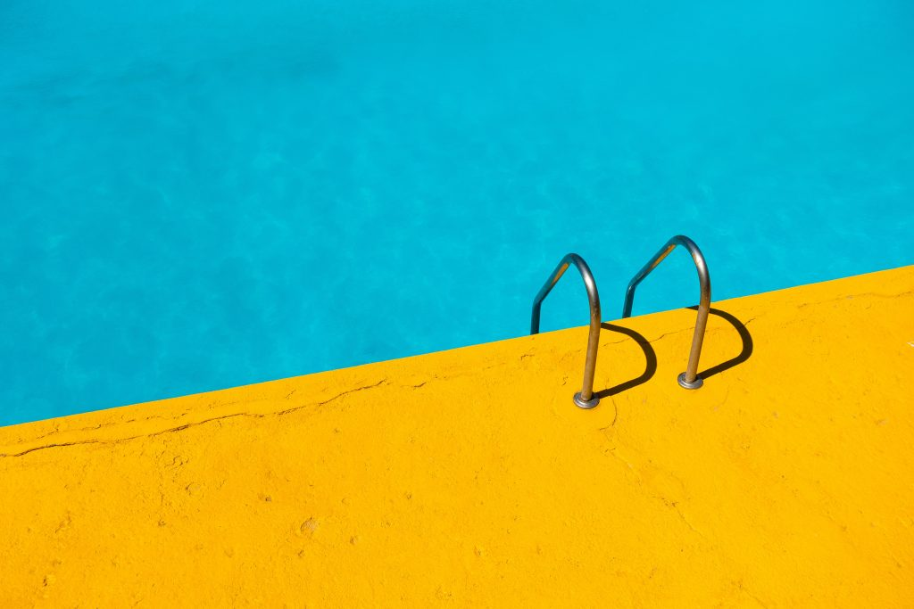 Image of blue water in a swimming pool next to a yellow concrete pad